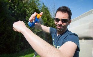 Un homme applique de la crème solaire sur son bras.