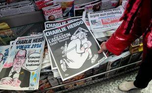 Une femme regarde dans un kiosque, le 6 janvier 2016 à Paris, le numéro spécial de Charlie Hebdo  paru un an après l'attentat
