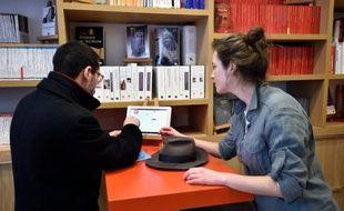 Des clients de la nouvelle librairie des Presses universitaires de France choisissent sur une tablette les livres qu'ils veulent imprimer, à Paris, le 16 mars 2016