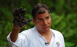 Le président équatorien Rafael Correa montre sa main couverte de pétrole près d'un puits exploité par Texaco, le 17 septembre 2013