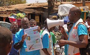 Des professionnels de la santé informent les habitants des risques du virus Ebola et des moyens de prévenir l'infection, à Conakry en Guinée, le 31 mars 2013.
