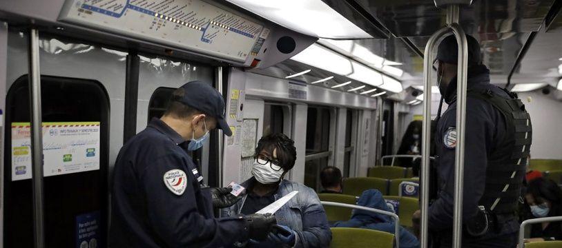 Des policiers effectuant des contrôles dans un RER le 15 mai 2020