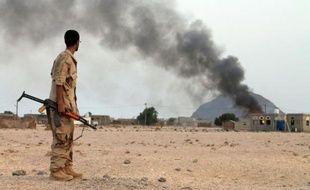 Un combattant yéménite des Comités de résistance populaire regarde de la fumée s'élever d'un bâtiment à l'ouest d'Aden, dans le sud du pays, le 12 juillet 2015