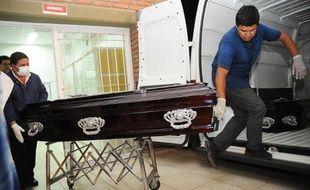 Des employés des pompes funèbres portent le cercueil d'un des huit Français morts dans le crash de leur hélicoptère pendant le tournage d'une émission télévisée en Argentine, le 17 mars 2015 à La Rioja, dans le nord-ouest du pays