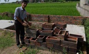 Nguyen Van Thao, un volontaire catholique vietnamien, montre de petits cercueils servant à enterrer des foetus dans un cimetière de la banlieue d'Hanoï, le 18 août 2014