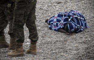Un homme gisant au sol après son arrivée sur le territoire espagnol à la frontière du Maroc et de l'Espagne, dans l'enclave espagnole de Ceuta, le mardi 18 mai 2021.