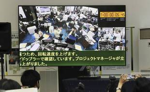 Le travail des scientifiques de l'agence spatiale japonaise retransmis à la télévision, le 5 décembre 2020.