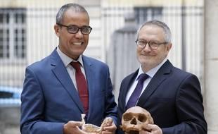 Le paléoanthropologue français Jean-Jacques Hublin (dr) et Abdelouahed Ben-Ncer (g) de l'Institut  National d'Archéologie du Maroc posent en tenant dans leurs mains le crâne d'un Homo Sapiens vieux de 300.000 ans, le 6 juin à Paris.