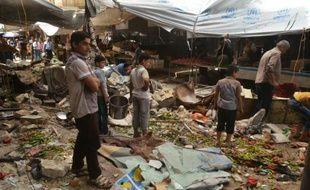 Des Syriens au milieu des décombres après des tirs attribués à des rebelles le 4 juin 2016 à al-Midan dans la banlieue d'Alep