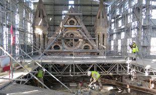 Sous le toit, les ouvriers travaillent à la restauration des voûts