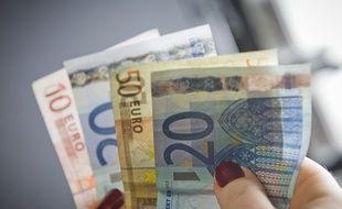 Paris le 04 fevrier 2013. Illustration argent billet de banque tenus dans une main.