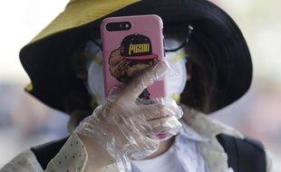 Une femme utilise des gants pour tenir son smartphone le 18 mars 2020 à Manille aux Philippines.