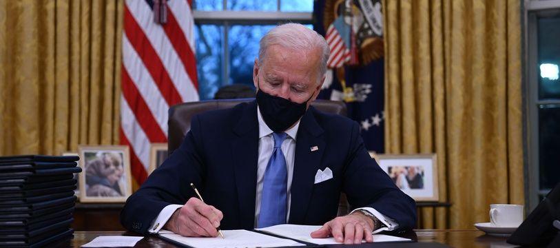 Joe Biden signe ses premiers décrets présidentiels, notamment pour rejoindre l'accord de Paris, le 20 janvier 2021 dans le bureau ovale de la Maison Blanche.