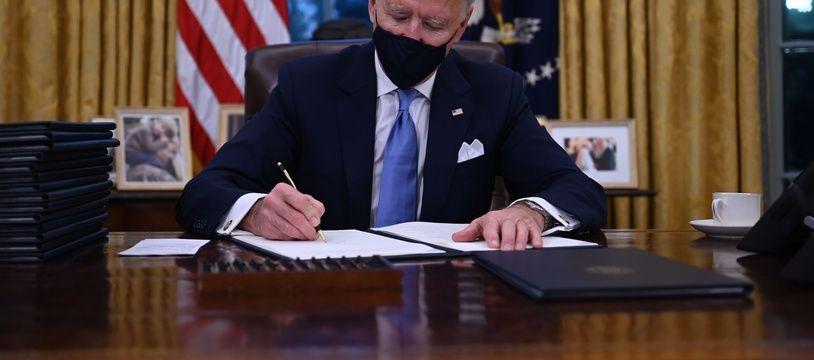 Joe Biden signe ses premiers décrets présidentiels, notamment pour rejoindre l'accord de Paris, le 20 janvier 2021 dans le bureau ovale de la Maison-Blanche.