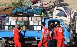 Des bénévoles de la Croix Rouge aident les réfugiés à rentrer en Syrie, le 23 juillet 2018.