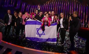 Netta porte le trophée de l'Eurovision 2018, entourée de ses danseuses et de sa délégation, sur la scène du concours à Lisbonne, le 13 mai 2018.