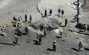 Des habitants autour d'un cratère provoqué par une frappe aérienne de la coalition arabe, le 1er octobre 2015 à Sanaa, au Yémen
