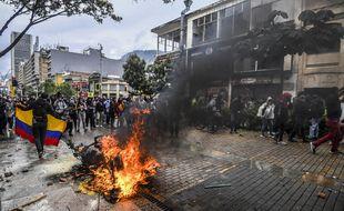 Des gens entourent une moto de police en flammes lors d'une manifestation contre un projet de loi de réforme fiscale lancé par le président colombien Ivan Duque, à Bogota, le 28 avril 2021.