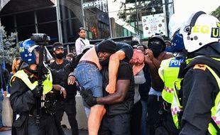 Un manifestant transporte un contre-manifestant blessé en lieu sûr, près de la gare de Waterloo lors d'une manifestation de Black Lives Matter - Londres, le 13 juin 2020