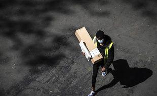 Paris, le 15 avril 2020. Un homme protégé d'un masque livre un colis Amazon en pleine épidémie de coronavirus.