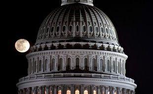 La lune se lève derrière le dome du Capitole, siège du congrès américain à Washington.