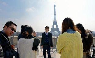 Des touristes chinois prennent des photos souvenir, le 27 mars 2013 devant la tour Eiffel à Paris