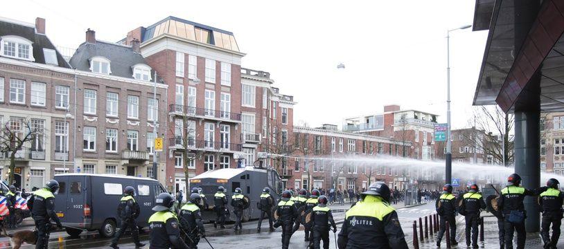 La police anti-émeute néerlandaise utilise des canons à eau pour disperser une manifestation anti couvre-feu, le 24 janvier 2021 à Amsterdam, aux Pays-Bas.