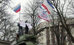 Kalachnikov à la main, des hommes en uniforme patrouillent à l'extérieur de l'aéroport de Simferopol, en Crimée, bien décidés à refouler d'éventuels nationalistes ukrainiens qui chercheraient à se rendre dans la capitale de cette presqu'île du sud de l'Ukraine en proie à de vives tensions séparatistes.