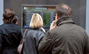Des personnes regardent les cours de la Bourse dans une rue de Paris