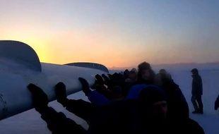 Capture d'écran d'une vidéo Youtube montrant des passagers pousser leur avion pour qu'il puisse décoller sur l'aéroport de la petite ville d'Igarka, en Sibérie, le 25 novembre 2014.