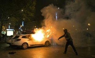 Un homme jette un projectile sur une voiture de police en feu place de la République à Paris, le 23 avril 2016