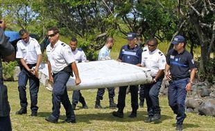 Des policiers transportent le débris d'avion suspect récupéré sur le littoral de l'île française de la Réunion, le 31 juillet 2015.