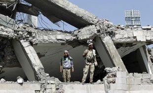 Des rebelles chiites Houthis inspectent les ruines d'un hôtel détruit par les raids de la coalition arabe, le 31 mai 2015 au nord de Sanaa, la capitale yéménite