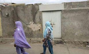 Deux femmes passent devant la maison de la jeune fille menacée de mort pour blasphème, à Islamabad.