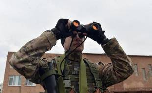 Un soldat ukrainien volontaire observe à la jummelle, le 26 février 2015 à Chermalyk, dans la région de Donetsk