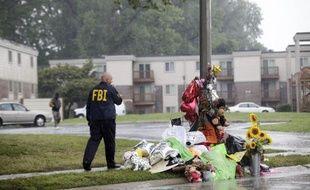 Un agent du FBI passe devant des fleurs déposées en hommage à Michael Brown, un jeune Noir de 18 ans tué par un policier il y a une semaine à Ferguson dans le Missouri le 16 août 2014