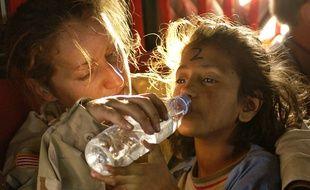 Une jeune Pakistanaise boit de l'eau potable pendant une opération humanitaire en 2007.
