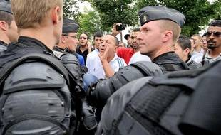 Un cordon de gendarme mobile protége le ministre de l'intérieur Manuel Valls qui est pris a parti par des habitants du quartier Nord d'Amiens à l'occassion de son déplacement le 14 Aout 2012 dans un quartier sensible d'Amiens aprés une nuit d'émeute ou plusieurs policiers ont été blésses.