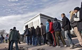 Des migrants attendent la distribution des repas sur le port de Calais.