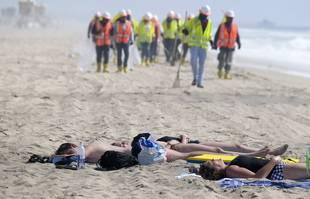 Des plagistes se reposent pendant que les travailleurs continuent de nettoyer la plage contaminée à Huntington Beach, en Californie, le lundi 11 octobre 2021.
