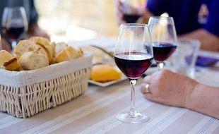 Un repas avec des verres de vin. (Illustration)