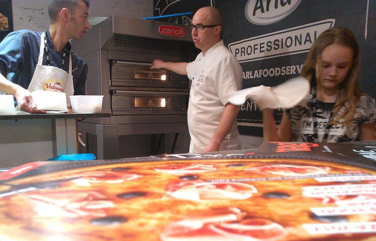 Paris, le 16 mars 2017. Napolitaine ou Hawaïenne sortent du four du champion de France de la pizza classique 2012, Grégory Edel (au centre). – C.Anger