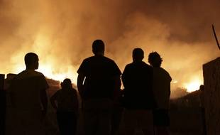 People watch a wildfire raging near houses in the outskirts of Obidos, Portugal, in the early hours of Monday, Oct. 16 2017. Wildfires in Portugal killed at least 27 people, injured dozens more and left an unconfirmed number of missing in the country's second such tragedy in four months, officials said Monday.