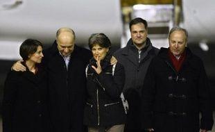 Claudia Priest (au c.) retrouvent ses proches en compagnie de Laurent Fabius (2e à g.) le 25 janvier 2015 à l'aéroport de Villacoublay