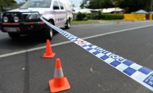 Un cordon de police empêche l'accès à la propriété où huit enfants ont été retrouvés morts et une femme blessée à Cairns, dans le nord-est de l'Australie, le 20 décembre 2014