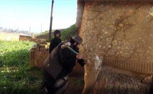 Image tirée d'une vidéo fournie par le groupe EI le 26 février 2015 montrant un militant détruisant une effigie de Lamassou, une divinité assyrienne, dans le nord du gouvernorat irakien de Ninive