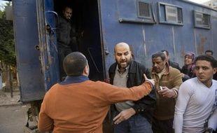 Un policier egyptien pousse un manifestant des Frères musulmans dans un fourgon, le 27 décembre 2013 au Caire