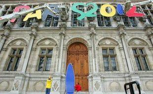 """Des techniciens enlèvent les lettres du logo """"Paris 2012"""" du fronton de l'Hôtel de Ville, le 8 juillet 2005 à Paris, deux jours après la victoire de Londres"""