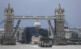 Un bateau navigue sur la Tamise à Londres, le lundi 9 août 2021 devant le Tower Bridge qui est bloqué en position complètement ouverte en raison d'un défaut technique.