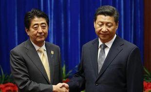 Poignée de mains entre le président chinois Xi Jinping (d) et le Premier ministre japonais Shinzo Abe au Palais du Peuple, en marge du sommet de l'Apec, le 10 novembre 2014 à Pékin